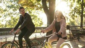 Feche acima dos pares ou dos amigos novos caucasianos que montam suas bicicletas no parque ou no bulevar vazio da cidade no verão video estoque