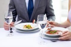 Feche acima dos pares que comem aperitivos no restaurante fotografia de stock