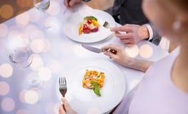 Feche acima dos pares que comem aperitivos no restaurante imagem de stock