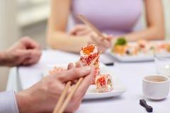 Feche acima dos pares que comem o sushi no restaurante Fotos de Stock Royalty Free