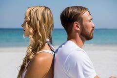 Feche acima dos pares que meditam na praia fotografia de stock royalty free