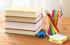 Feche acima dos pastéis ou os lápis e os livros da cor Foto de Stock