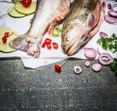 Feche acima dos peixes frescos com cozimento de ingredientes no fundo rústico, vista superior imagens de stock royalty free