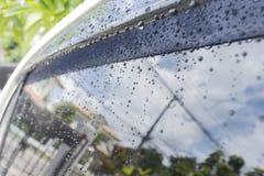 Feche acima dos pingos de chuva no carro e no vidro Fotos de Stock