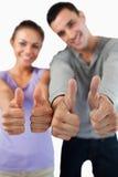 Feche acima dos polegares acima que estão sendo dados por pares novos Fotos de Stock Royalty Free