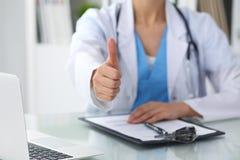 Feche acima dos polegares fêmeas do doutor acima Médico moreno de sorriso alegre feliz pronto para examinar o paciente medicina Fotografia de Stock