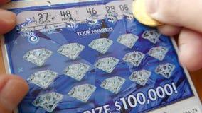 Feche acima dos povos que riscam o bilhete de loteria em casa vídeos de arquivo
