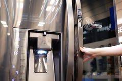 Feche acima dos povos que tentam um refrigerador novo dentro da loja eletrônica fotografia de stock royalty free