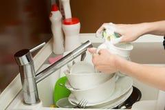 Feche acima dos pratos de lavagem na cozinha imagens de stock royalty free