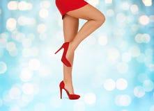 Feche acima dos pés da mulher elevação vermelha em sapatas colocadas saltos Fotografia de Stock