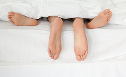 Feche acima dos pés do par em sua cama Fotografia de Stock