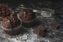 Feche acima dos queques do cacau com crosta de gelo do chocolate na tabela rústica c fotos de stock