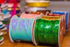 Feche acima dos rolos brilhantes das lantejoulas coloridas verdes e da fita azul, multi-coloridos sobre uma tabela de madeira no  Foto de Stock Royalty Free