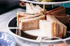 Feche acima dos sanduíches na bandeja servindo cerâmica de 3 séries para comer com chá quente fotografia de stock royalty free