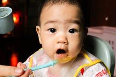 Feche acima dos sete meses pequenos felizes do filho idoso em veem através do babador plástico que come na cadeira para bebês dep imagem de stock