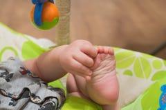 Feche acima dos toques do bebê seu próprio pé imagem de stock