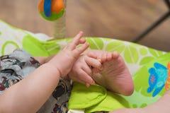 Feche acima dos toques do bebê seu próprio pé fotografia de stock royalty free