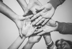 Feche acima dos trabalhos de equipe novos que unem suas m?os para uma colabora??o nova - amigos alegres motivados em um plano imagem de stock royalty free