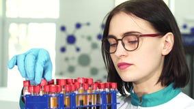 Feche acima dos tubos de ensaio de exame de um pesquisador fêmea novo com amostras de sangue video estoque