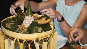 Feche acima dos turistas que tasing a placa tradicional do rijstafel do prato do balinese no jantar filme