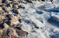 Feche acima em gelo quebrado em uma costa rochosa fotografia de stock royalty free