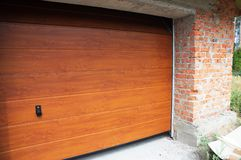 Feche acima em instalar placas da porta da garagem na construção nova da casa do tijolo Foto de Stock