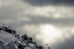 Feche acima em rochas na costa com a luz solar do céu nebuloso que reflete no oceano da água no fundo preto e branco do sepia fotos de stock