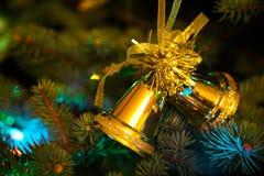 Feche acima em sinos dourados na árvore de Natal Imagens de Stock