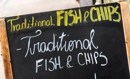 Feche acima em um sinal do peixe com batatas fritas, peixe com batatas fritas tradicional escrito em um quadro-negro na rua Foto de Stock Royalty Free