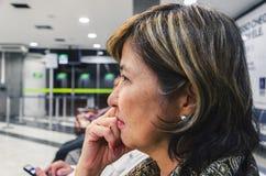 Feche acima em uma espera da mulher ansiosa na partida l do ` s do aeroporto Imagem de Stock Royalty Free