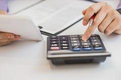Feche acima, homem de negócio ou contador do advogado que trabalham em contas usando uma calculadora e escrevendo em originais Foto de Stock Royalty Free