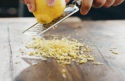 Feche acima a mão masculina da tabela de madeira friccionada do limão do ralador Fotos de Stock