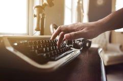 Feche acima, mão que datilografa em uma máquina de escrever velha na casa imagens de stock royalty free