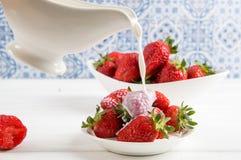 Feche acima, macro Franc?s Provence Algu?m derrama o creme do leite em uma placa de morangos vermelhas deliciosas imagem de stock royalty free