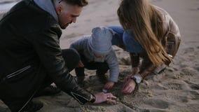 Feche acima a metragem de pais novos com seu menino da criança da criança que joga com a areia no tempo ventoso nebuloso frio, ho vídeos de arquivo