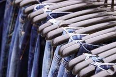 Feche acima muitas calças de brim que penduram na cremalheira fotografia de stock royalty free