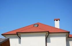 Feche acima na janela da claraboia do sótão da casa com o telhado vermelho do metal, calha, chaminé Imagem de Stock Royalty Free
