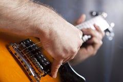 Feche acima na mão do ` s do homem que joga a guitarra Fotos de Stock