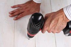 Feche acima na mão masculina usando a broca elétrica Homem que faz DIY em casa Imagens de Stock
