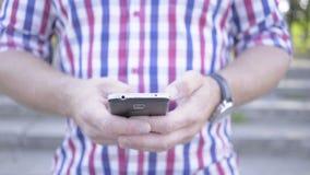 Feche acima nas mãos do ` s do homem que consultam o smartphone tiro do slider filme