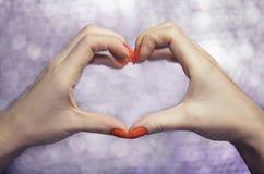 Feche acima nas mãos fêmeas bonitas com tratamento de mãos vermelho na forma do coração do amor Imagem de Stock Royalty Free