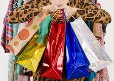 Feche acima nas mãos fêmeas que guardam muitos sacos de compras Foto de Stock