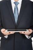 Feche acima nas mãos masculinas que guardam a tabuleta digital Imagem de Stock Royalty Free