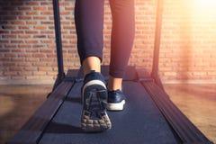 Feche acima no atleta da sapata, mulher que corre em um gym em uma escada rolante efeito do exercício e da luz solar, aptidão e e foto de stock royalty free