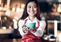Feche acima no café acima com o barista asiático da mulher do borrão que guarda a caneca Fotos de Stock