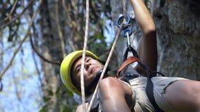 Feche acima no indivíduo asiático bonito que rappelling do penhasco na selva Extremamente perigoso video estoque
