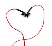 Feche acima nos earbuds vermelhos isolados no fundo branco (o trajeto de grampeamento) Fotografia de Stock Royalty Free