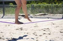 Feche acima nos pés que andam na corda-bamba ou no slackline exterior no th Imagens de Stock