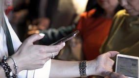Feche acima para as mãos da mulher com os braceletes que tomam a imagem de alguma informação em um outro telefone esperto em um p filme