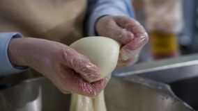 Feche acima para as m?os em cozinhar as luvas que preparam o mozzarella, conceito do alimento Quadro Trabalhador da f?brica de qu video estoque
